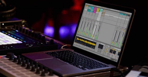 laptop displaying ableton live, next to an ableton push and arturia beatstep in a night club setting
